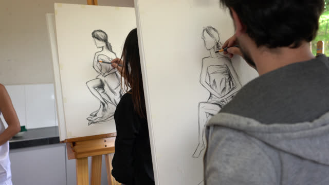 unrecognizable students drawing on canvas with charcoal while looking at a female model - art class stock videos & royalty-free footage
