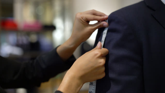 unrecognizable tailor measuring the at length of the suit of a customer - instrument of measurement stock videos & royalty-free footage