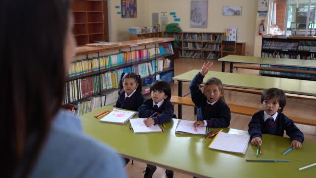 vidéos et rushes de enseignante méconnaissable posant une question à ses élèves pendant qu'ils lèvent la main et l'un d'eux répond - niveau primaire