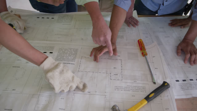 unrecognizable team of people working at a construction site all gathered around a table looking at a blueprint - reflective clothing stock videos & royalty-free footage