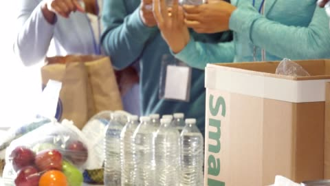 vídeos y material grabado en eventos de stock de irreconocible equipo de voluntarios organizan alimentos donados en banco de alimentos - voluntario