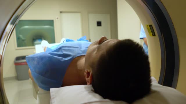 vídeos de stock, filmes e b-roll de técnico irreconhecível, verificando o paciente está configurado corretamente para uma rm - exame de ressonância magnética