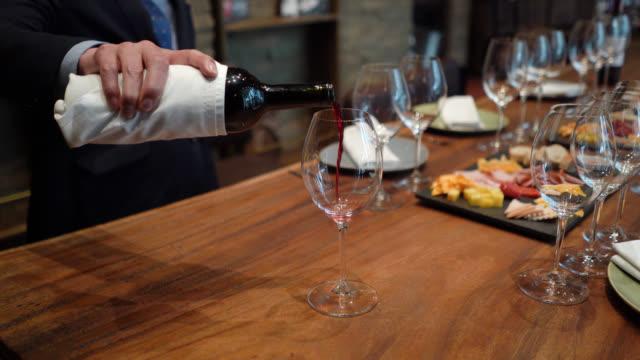 ワインテイスティングクラスの準備をするワインを提供する認識できないウェイター - ワインバー点の映像素材/bロール