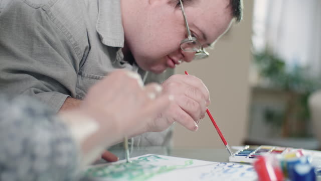 unrecognizable woman and smiling man with down syndrome painting picture together - intellectual disability stock videos & royalty-free footage