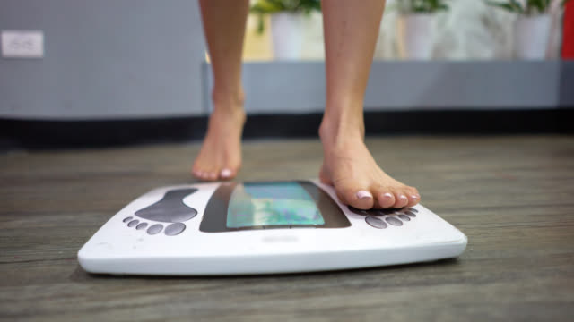unrecognizable woman at the gym getting on the scale - comparison stock videos and b-roll footage