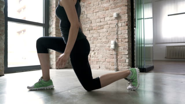 unrecognizable woman doing jump lunges at home - buttocks stock videos & royalty-free footage
