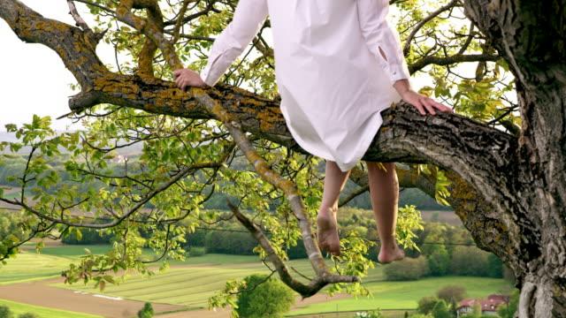 vídeos y material grabado en eventos de stock de slo mo irreconocible mujer disfrutando de la naturaleza mientras estaba sentado en un árbol - camisa blanca