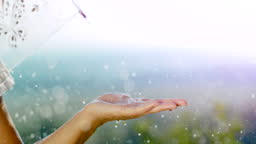 SUPER SLO MO Unrecognizable woman holds her open palm to the raindrops