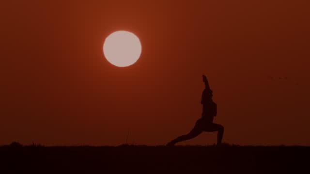 stockvideo's en b-roll-footage met slo mo ws onherkenbare vrouw in silhouet die rekoefeningen bij zonsondergang doet - jogster
