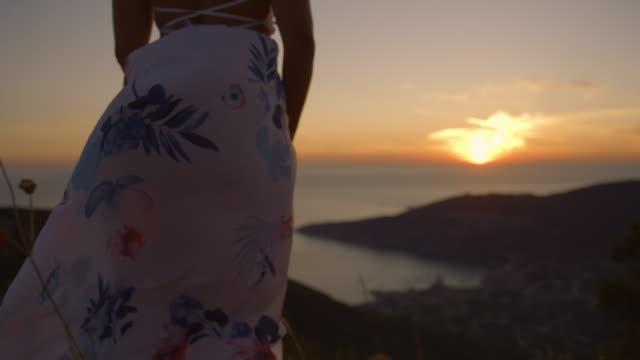 slo mo unrecognizable woman in white dress enjoying the amazing seaview and the beautiful sunset - dress stock videos & royalty-free footage