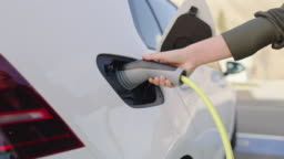SLO MO Unrecognizable woman inserting an EV plug into a vehicle inlet on a parking lot