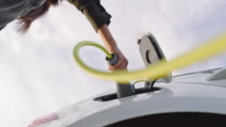 SLO MO Unrecognizable woman inserting an EV plug into a vehicle inlet