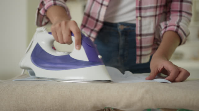 unrecognizable woman ironing a men's button down shirt at home - shirt stock videos & royalty-free footage