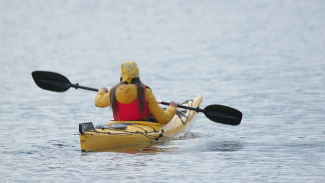 stockvideo's en b-roll-footage met unrecognizable woman kayaking in mountain lake. paddling and eco tourism. - hoofddeksel