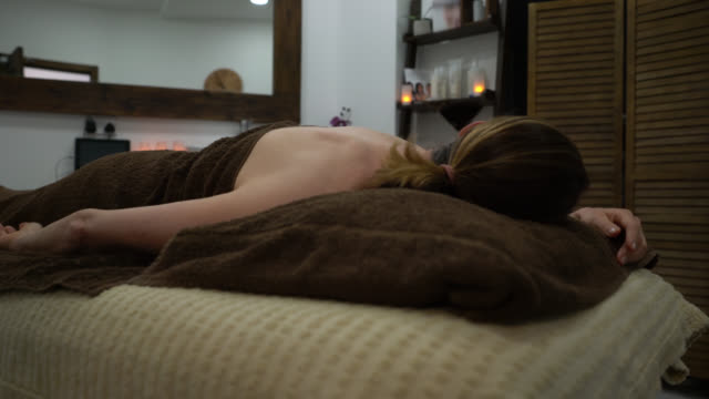 unrecognizable woman lying down relaxing after a back massage at the spa - massage table stock videos & royalty-free footage