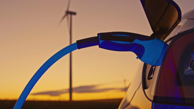 slo mo unkenntliche frau, die in der dämmerung einen ev-stecker in ihr auto steckt. sie lädt ihr elektrofahrzeug mit blauer energie, die von windkraftanlagen angetrieben wird. - station stock-videos und b-roll-filmmaterial