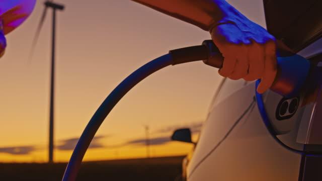 vidéos et rushes de slo mo femme méconnaissable brancher une prise ev dans sa voiture au crépuscule - ligne à haute tension