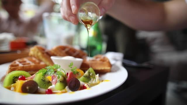 vídeos y material grabado en eventos de stock de mujer irreconocible vertiendo jarabe en waffles - waffles belgas