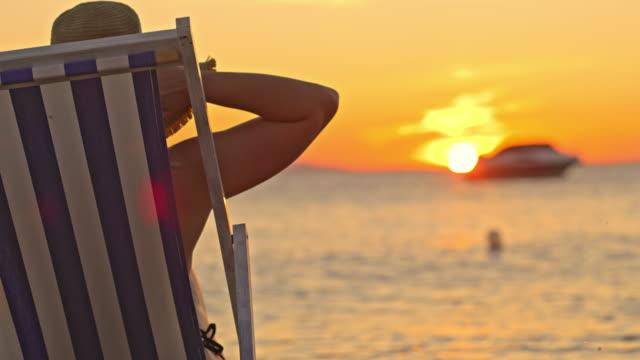 vídeos de stock, filmes e b-roll de slo mo mulher irreconhecível levantando os dois braços para o céu enquanto desfruta do pôr do sol na praia - braço humano
