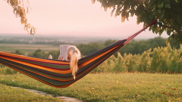 ds oigenkännlig kvinna läser en bok i en hängmatta - hängmatta sol bildbanksvideor och videomaterial från bakom kulisserna