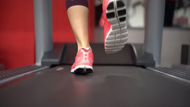unrecognizable woman running on a treadmill at the fitness center - treadmill stock videos & royalty-free footage