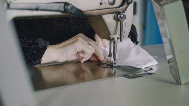 slo mo unrecognizable woman sewing homemade masks - a helping hand stock videos & royalty-free footage