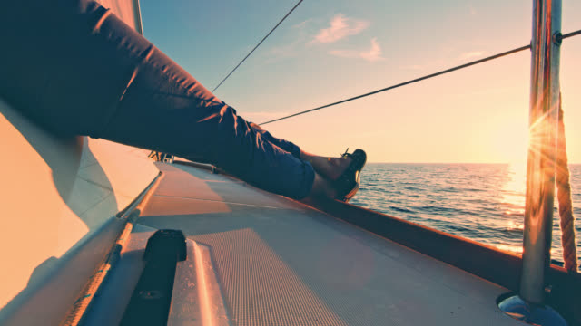 ws unrecognizable woman sitting on a sailboat at sunset - ponte di una nave video stock e b–roll