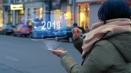 Unrecognizable woman standing on the street interacts HUD hologram 2019