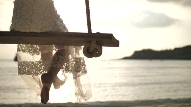 木のブランコで揺れる認識できない女性 - 白のドレス点の映像素材/bロール
