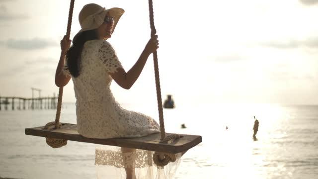 vídeos y material grabado en eventos de stock de mujer irreconocible balanceándose en un columpio de árbol - columpio
