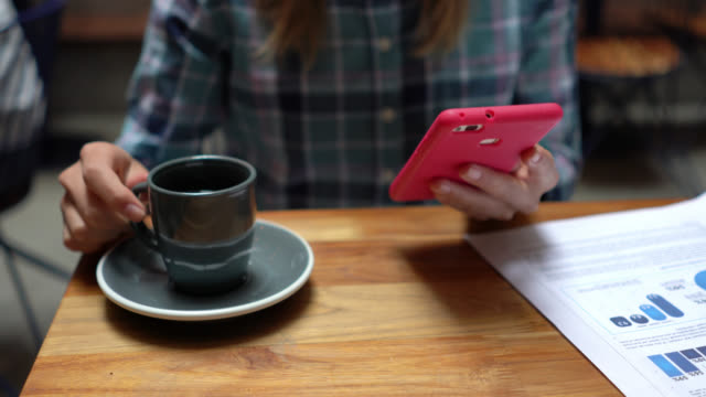 unrecognizable woman taking a break from work enjoying a coffee and chatting on smartphone - unrecognizable person stock videos & royalty-free footage