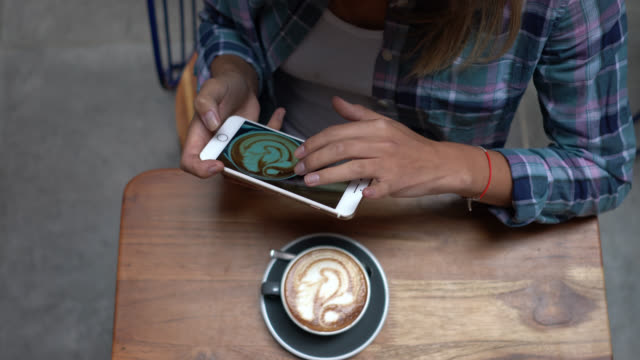 unrecognizable woman taking a picture of her cappuccino with a smartphone - photograph stock videos & royalty-free footage