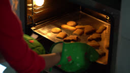 Unrecognizable woman taking out christmas cookies from the oven on tray