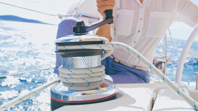 MS Unrecognizable woman turning a winch while navigating a sailboat