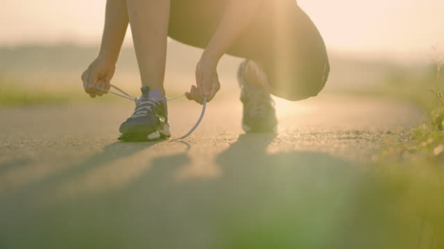 slo mo unrecognizable woman tying shoelaces while jogging - tie stock videos & royalty-free footage