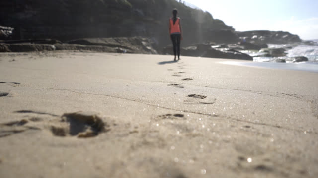 unrecognizable woman walking at the beach barefoot leaving footprints on sand - footprint stock videos and b-roll footage