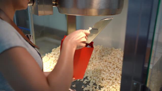vídeos de stock, filmes e b-roll de mulher unrecognizable que trabalha no carrinho de concessão de um milho do pnf do serviço do teatro de cinema - fazer