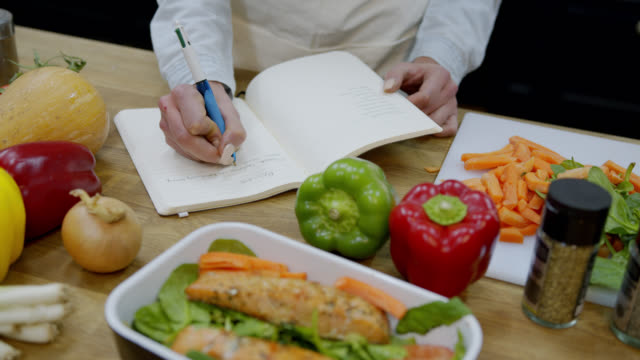 unrecognizable woman writing down a recipe on notepad at the kitchen counter with delicious vegetables and food on foreground - blocco per appunti video stock e b–roll