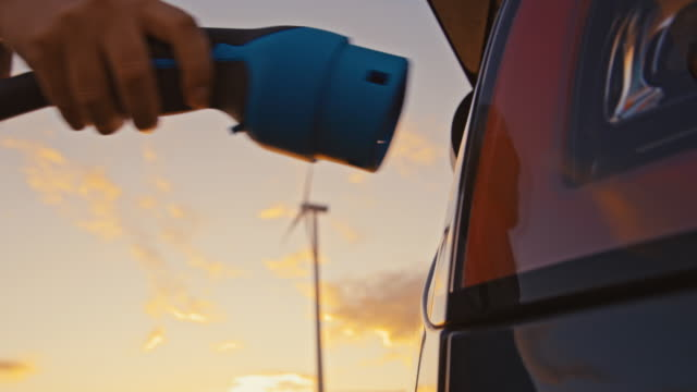 slo mo unrecognizable woman's hand unplugging an ev plug into a car for charging - wired stock videos & royalty-free footage