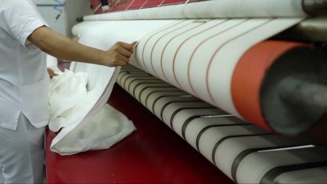 unerkennbare frauen bügeln blätter auf industrieller bügelmaschine - waschsalon stock-videos und b-roll-filmmaterial