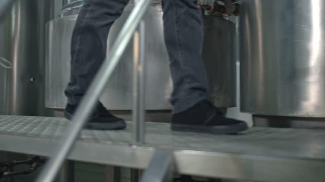 slo mo 認識できない作業者が工場を歩く、クローズアップ - safety点の映像素材/bロール