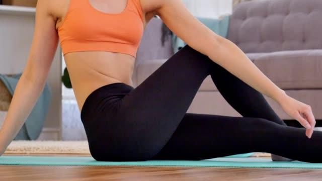 unrecognizable young does floor exercises in her home - twisted stock videos & royalty-free footage
