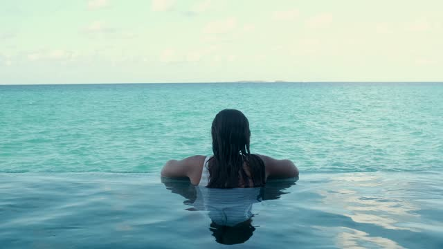 unrecognizable young lady recreating in swimming pool and admiring ocean - wet hair stock videos & royalty-free footage