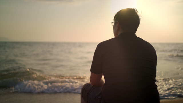 unrecognized man sitting day dreaming by the sea - depression land feature stock videos & royalty-free footage