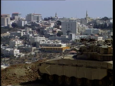 unrest continues; itn israeli tank overlooking town as turret traverses cms ditto - 見渡す点の映像素材/bロール