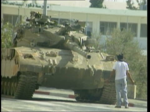 unrest continues; itn west bank: bethlehem: ext palestinian man standing in front of israeli tank as turret traverses palestinians pushing bin along... - barricade stock videos & royalty-free footage