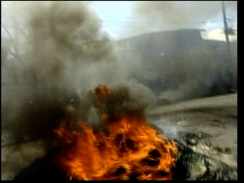 port au prince gvs tyres burning in street lms trucks full of armed government supporters along looking for trouble i/c - itv late news stock-videos und b-roll-filmmaterial