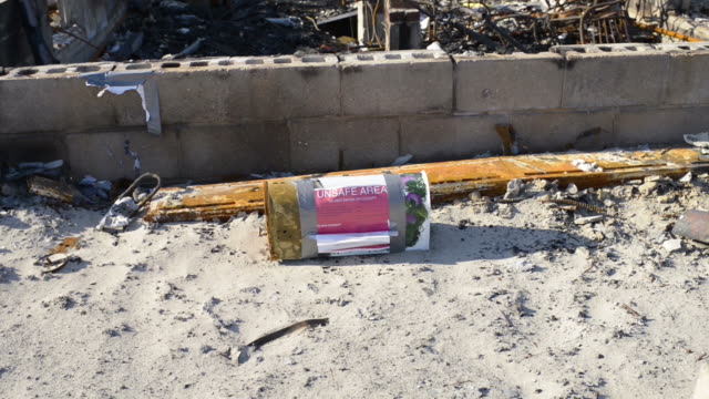 stockvideo's en b-roll-footage met unsafe sign attached to a letterbox on the floor by a destroyed house - breedbeeldformaat