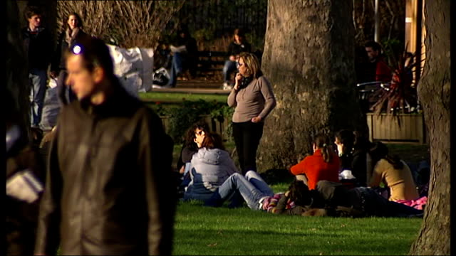 Unseasonably warm February weather ENGLAND London EXT People strolling about and sitting on grass in February sunshine in Russell Square Gardens...