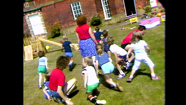 unsteady shot of pre-school children playing outdoors; 1984 - nursery school building stock videos & royalty-free footage